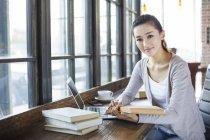 Femme chinoise assise avec livre dans un café — Photo de stock