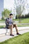 Empresario chino usando laptop en zona verde - foto de stock