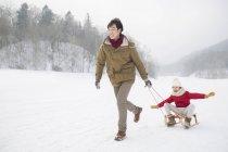 Chino padre corriendo y tirando a hija en trineo - foto de stock