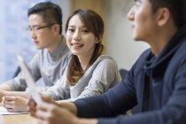 Mujer China sonriendo en reunión con sus colegas en la sala de juntas - foto de stock