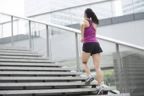Chinese woman running up on stairs — Stock Photo