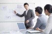 Китайские бизнесмены обсуждают стратегию на доске — стоковое фото
