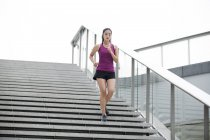 Chinese woman running down on stairs — Stock Photo