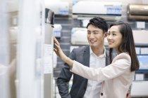 Китайская пара, покупка кондиционера воздуха в электроники магазин — стоковое фото