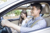 Chinese couple sitting in car and smiling — Stock Photo