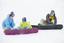 Chinese parents wearing snowboarding gear on son — Stock Photo