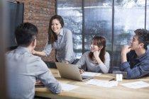 Collaboratori cinesi seduti nella sala riunioni con laptop — Foto stock