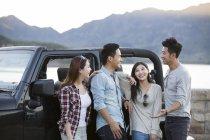 Amigos chineses conversando na frente de carro no subúrbio — Fotografia de Stock