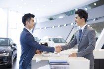 Китаец, Пожатие руки дилера автомобилей в салоне — стоковое фото