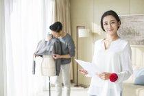 Chinesische weibliche Mode-Designer mit Skizzen während Mann arbeiten — Stockfoto