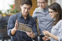 Chinese IT workers developing digital tablet — Stock Photo