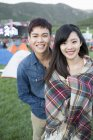 Chinese couple posing at music festival camping — Stock Photo