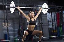 Китаянка поднимает штангу в спортзале — стоковое фото