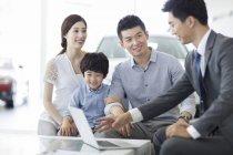 Китайский автодилер сидит с клиентами семьи в выставочном зале — стоковое фото