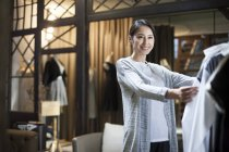 Mature Chinese boutique owner checking clothes on rack — Stock Photo