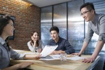 Colleghi cinesi che discutono di lavoro in sala riunioni — Foto stock