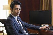 Retrato de hombre de negocios chino en escritorio de oficina en casa - foto de stock