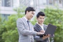 Colegas de trabalho chineses trabalhando com laptop na rua — Fotografia de Stock