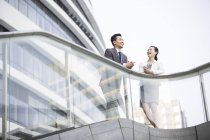 Chinese business people leaning on balustrade and talking — Stock Photo