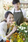 Chinese woman smelling roses in store with florist — Stock Photo