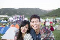 Китайская пара, завернутый в одеяло, обнимая фестиваля кемпинг — стоковое фото
