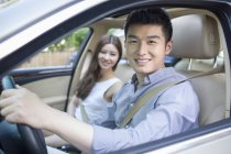 Chinese couple sitting in car and looking in camera — Stock Photo