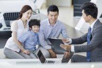 Chinesische Autohändler sitzen mit Kunden Familie im showroom — Stockfoto