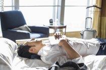 Empresário chinês descansando na cama no quarto de hotel — Fotografia de Stock