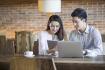 Chinese man and woman using digital tablet and laptop in cafe — Stock Photo