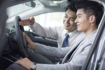 Concessionario auto che aiuta uomo con test drive — Foto stock