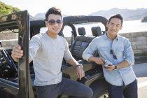Uomini cinesi appoggiati su auto in periferia e guardando in macchina fotografica — Foto stock