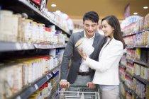 Китайская пара, выбор товаров в супермаркете — стоковое фото