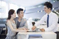 Casal chinês comprando carro no showroom — Fotografia de Stock