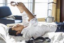 Empresário chinês usando tablet digital no quarto de hotel — Fotografia de Stock