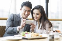 Chinese couple taking photo with smartphone in restaurant — Stock Photo