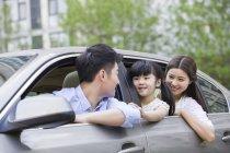 Китайская семья езда и выступающие из автомобиля — стоковое фото