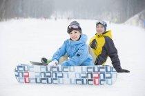Couple chinois assis avec planches à neige sur neige — Photo de stock