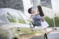 Chinese couple embracing next to car — Stock Photo