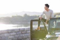 Chino hombre de pie en el coche en los suburbios - foto de stock