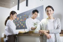 Chinese restaurant owner leaning on counter with wait staff — Stock Photo