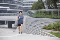 Chinese man jogging on street — Stock Photo