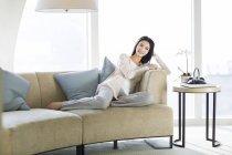 Femme chinoise assise sur le canapé dans le salon intérieur — Photo de stock
