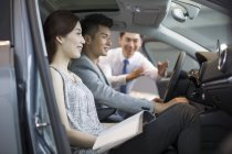 Concessionário de carro chinês ajudando casal escolher carro no showroom — Fotografia de Stock