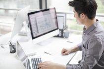 Homem de negócios chinês usando laptop no escritório — Fotografia de Stock