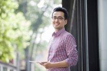 Homem chinês segurando tablet digital e olhando para longe — Fotografia de Stock
