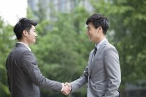 Chinese business person shaking hands on street — Stock Photo