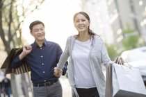 Mature chinese couple with shopping bags in city — Stock Photo