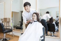Chinese barber with female customer looking in mirror — Stock Photo