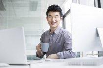 Chinesischer Geschäftsmann trinkt Kaffee am Arbeitsplatz — Stockfoto
