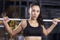 Femme chinoise en soulevant des haltères au gymnase — Photo de stock
